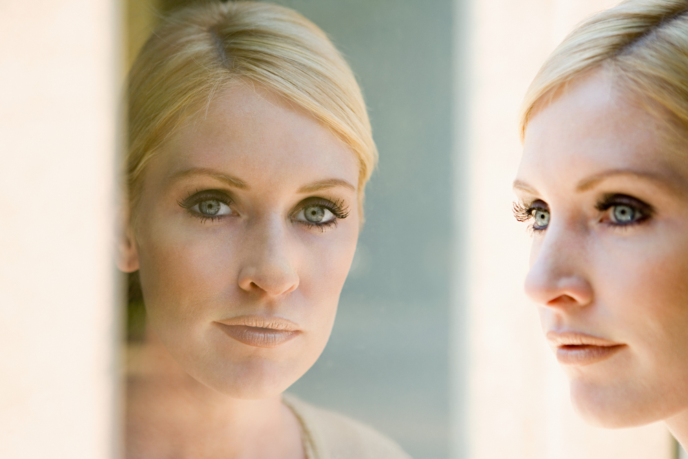 Woman gazing into mirror with imposter syndrome